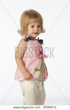 Little Girl In Pink Standing Holding Shirt