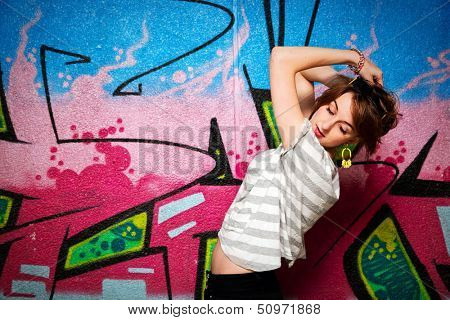 Stylish fashionable girl in a dance pose against colorful graffiti wall. Fashion, trends, subculture.