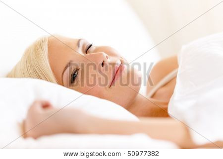 Close up of lying in bed woman on white pillow