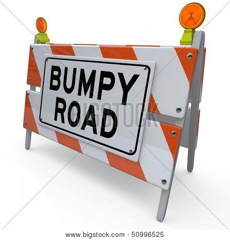 The words Bumpy Road on a barrier or blockade as a warning sign that trouble, problems, issues or obstacles lie ahead in your future