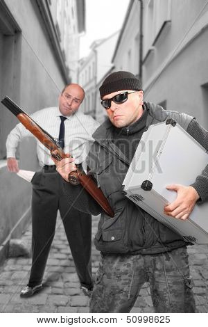 Dangerous gangster with shotgun and his victim. Street assault or bank robbery.