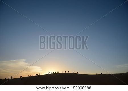 Group of people on horizon silhouetted against setting sun