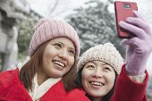 stock photo of two women taking cell phone  - Two friends taking picture with cell phone in snow - JPG