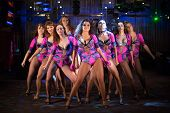 Nine beautiful showgirls in purple costumes posing on stage poster
