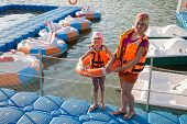 stock photo of dock a pond  - Mother and daughter on the dock with round inflatable boats with electric motor - JPG