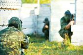 image of paintball  - Two paintball sport players in prootective uniform and mask aiming and shoting with gun outdoors - JPG