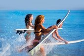 stock photo of sprinkling  - Boys and girls teen surfers running jumping on surfboards at the beach - JPG