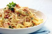 stock photo of carbonara  - Fettucine carbonara in a white bowl garnished with parmesan and parsley - JPG