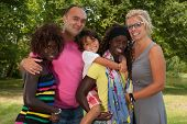 stock photo of multicultural  - Happy multicultural family having a nice summer day - JPG