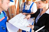 stock photo of real-estate-team  - Construction site team or architect and builder or worker with helmets controlling or having discussion of plan or blueprint - JPG