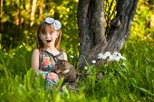 stock photo of fanny  - Little fanny girl playing with a cat in the park - JPG