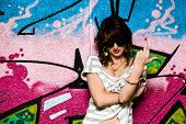 pic of fuck  - Stylish fashionable girl showing fuck off middle finger gesture against colorful graffiti wall - JPG