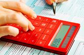 stock photo of economy  - Hands of accountant with calculator and pen - JPG