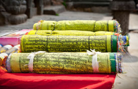 stock photo of sanscrit  - Buddhist Tibetan prayer flags rolled into a roll - JPG
