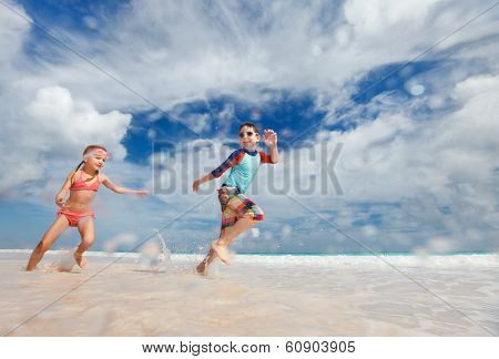 Happy kids running and jumping at beach