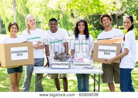 Portrait of young confident volunteers with donation boxes in park