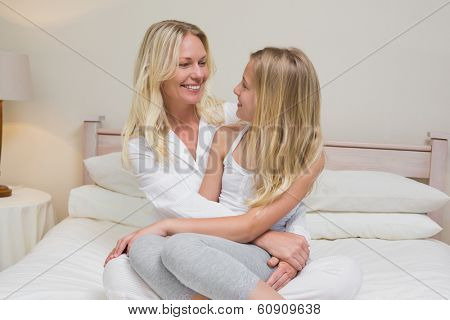 Smiling mother and daughter looking at each other in bed at home