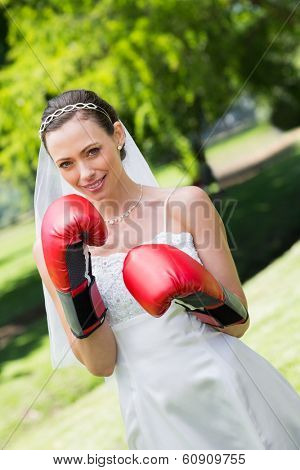 Portrait of happy young bride with red boxing gloves in park