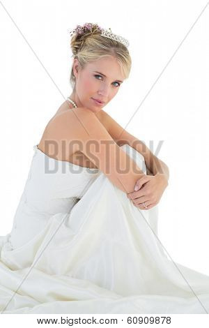 Portrait of sensuous bride hugging knees over white background