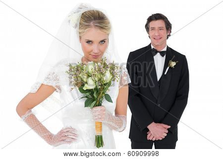 Portrait of sensuous bride smelling flowers while groom standing in background over white