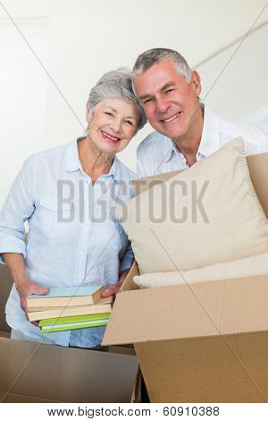 Happy senior couple moving into new home smiling at camera