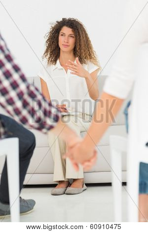 Therapist looking at reconciled couple holding hands at therapy session