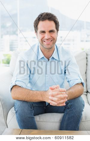 Attractive man sitting on the couch smiling at camera at home in the living room