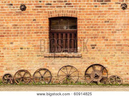 Row Of Old Rusty Cart Wheels Against Barn