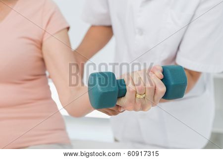 Mid section of female physiotherapist assisting senior woman to lift dumbbell in the medical office