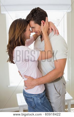 Side view of a loving young couple looking at each other at home