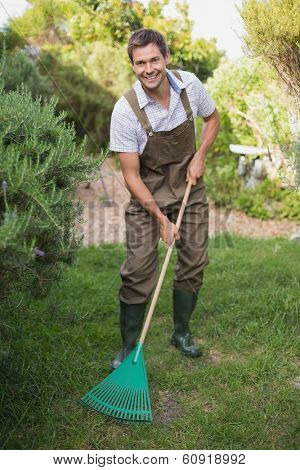 Full length portrait of a young man in dungarees raking the garden