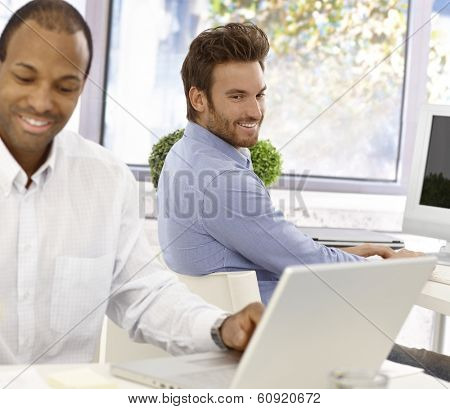 Young office worker peeping his colleagues screen, smiling.