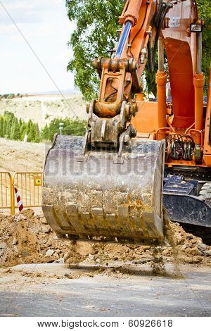 Loader Excavator standing in quarry with risen bucket over cloudscap