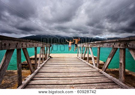 Couple jumping off a jetty into the sea on a tropical island