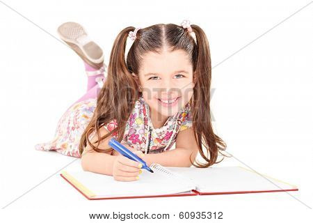 Little girl laying on the floor and drawing pictures in a notebook isolated on white background