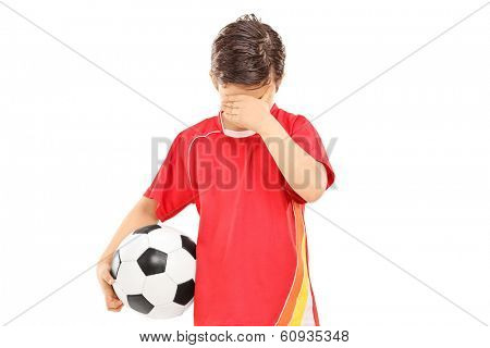 Sad boy with soccer ball isolated on white background