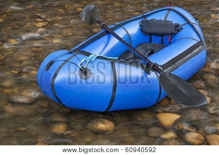 a blue packraft (one-person light raft used for expedition or adventure racing) with a kayak paddle against a shallow river