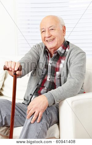 Happy old man with cane sitting at home on a sofa