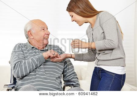 Woman giving senior man in wheelchair medical pill with a glass of water