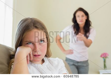 Bored girl with mother scolding her in background at home