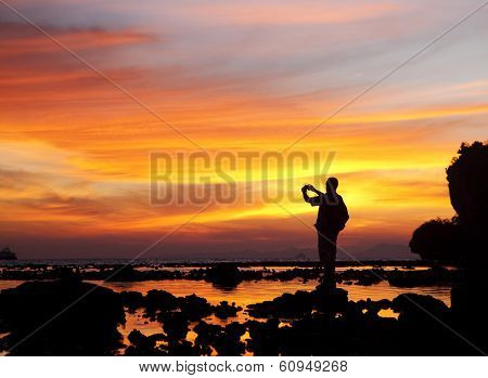 Man watching sunset and taking photos on Railay beach, Krabi, Thailand