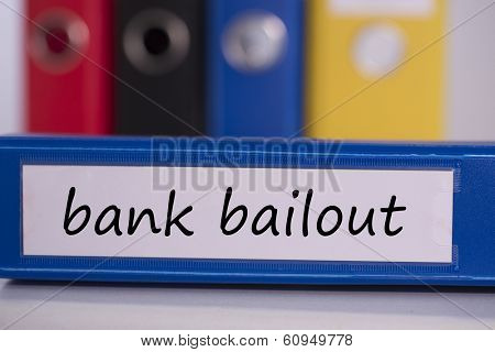 The word bank bailout on blue business binder