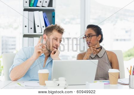 Partners working together at desk on laptop in creative office