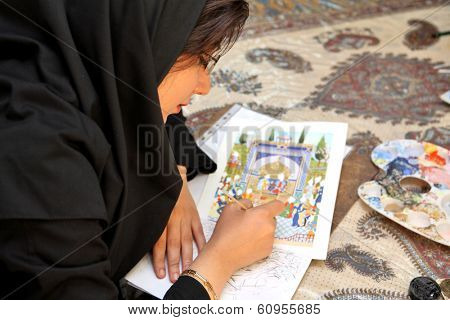 ESFAHAN, IRAN - DECEMBER 01, 2007:  Muslim woman artist in black headscarf paints traditional Persian miniature