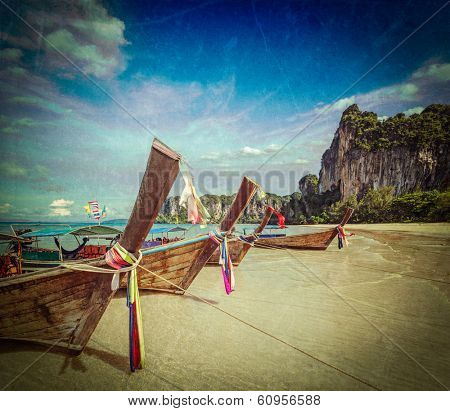 Vintage retro hipster style travel image of Long tail boats on tropical beach (Railay beach) in Thailand with grunge texture overlaid