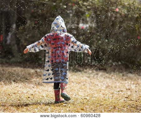 little girl in raincoat playing in the rain