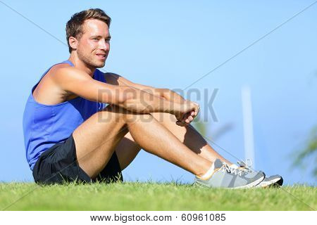 Sport fitness man relaxing after training outdoor. Young male athlete resting relaxing sitting in grass after running and training exercise outside in summer. Caucasian man sports model.