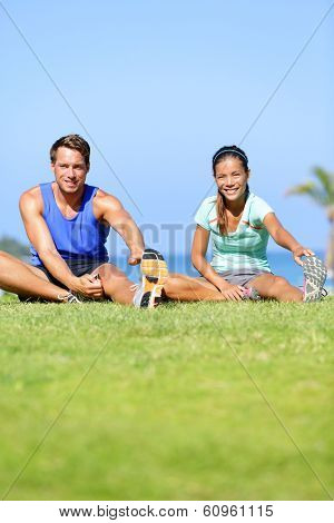 Fitness people - couple stretching exercises outdoors. Fit woman and man doing hamstring leg stretch exercise and stretches workout outdoor in summer. Beautiful multiracial couple.