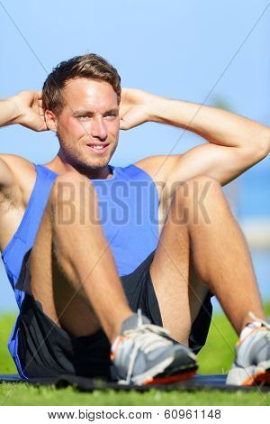 Man doing sit-ups outdoor. Male fitness model training sit up exercise during outside workout in grass in summer. Handsome muscular male sport model working out.