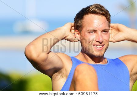 Fitness man doing sit-ups outdoor. Close up portrait of male fitness model training sit up exercise during outside workout in grass in summer. Handsome muscular male sport model working out.